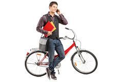 Student holding books and talking on a phone. Full length portrait of a smiling student holding books and talking on a phone next to a bike  on white background Royalty Free Stock Photos
