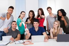 Student holding degree with classmates gesturing thumbs up. Portrait of college student holding degree with classmates gesturing thumbs up in classroom Royalty Free Stock Images