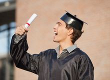 Student Holding Diploma On Graduation Day In. Excited male student holding diploma on graduation day in college Stock Photo