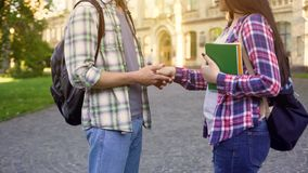 Student holding girlfriend hand, spontaneous dating near college, relations royalty free stock images