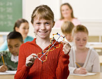 Student holding helix in classroom. Student holding a model of a double helix in the classroom stock photography