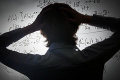 Student holding his head looking at complex math formulas on whiteboard. Problem to solve Royalty Free Stock Photo
