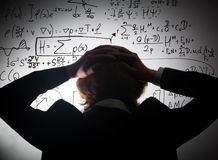Student holding his head looking at complex math formulas on whiteboard. Problem to solve. Student holding his head looking at complex math formulas on Stock Photo