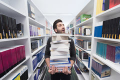 Student holding lot of books in school library Stock Photo
