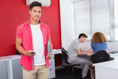 Student holding notebook and phone near classmates. At the college Stock Photos