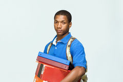 Student Holding Notebooks - Horizontal. Male student wearing a backpack carries notebooks and boxes. Horizontally framed photograph Royalty Free Stock Image