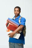 Student Holding Notebooks - Vertical. Male student wearing a backpack carries notebooks and boxes.  He looks frustrated. Vertically framed photograph Stock Image