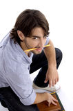 Student holding pencil in mouth Stock Images