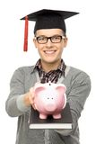 Student holding piggybank Royalty Free Stock Images