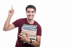 Student holding pile of books having good idea. And smiling isolated on white background with copypsace advertising area stock image