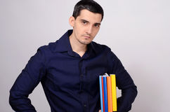 Student holding a pile of books under his arm. Teacher with colorful books in his hand. Royalty Free Stock Image