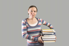 Student holding stack of books. Stock Photo