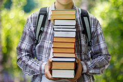 Student holding a stack of textbooks . Concept of heavy study Royalty Free Stock Photo