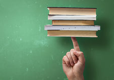Student holding up books with A Finger Royalty Free Stock Image