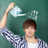 Student Holding Watering Can With Question Marks On Chalkboard Royalty Free Stock Photography