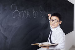 Student holds book with text Back to School. Male primary school student holding a book and smiling at the camera while writing text of Back to School on the Stock Photos
