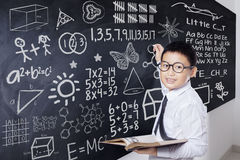 Student holds book and write formula. Male student smiling at the camera while holding a book and writing mathematics formula on the blackboard Stock Image