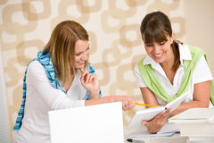 Student at home - two woman with book and laptop Stock Photo
