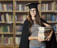 Student i böcker för utbildning för avläggande av examenhatt hållande, ledar- kvinna royaltyfria bilder