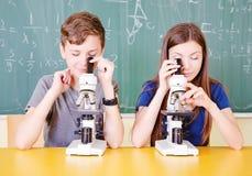 Student i klassrum genom att använda ett mikroskop Arkivfoton