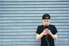 Student i lock och skjorta som lyssnar till musik på hörlurar som skriver på din telefon Arkivbilder