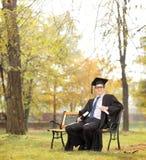 Student im Aufbaustudium, der Diplom und Buch im Park hält Lizenzfreie Stockbilder