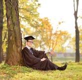 Student im Aufbaustudium, der durch einen Baum in einem Park sitzt Stockfotos