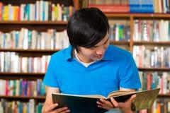 Student im Bibliothekslesebuch Stockbilder