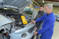Student with instructor repairing car during apprenticeship. Student with instructor repairing a car during apprenticeship stock photography