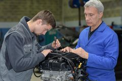 Student with instructor repairing car during apprenticeship. Student with instructor repairing a car during apprenticeship royalty free stock photos