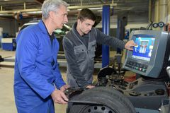 Student with instructor repairing car during apprenticeship. Student with instructor repairing a car during apprenticeship royalty free stock images