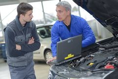 Student with instructor repairing car during apprenticeship. Student with instructor repairing a car during apprenticeship royalty free stock photo