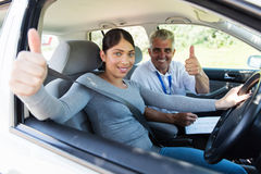 Student instructor thumbs up. Portrait of happy student driver and instructor giving thumbs up Stock Photography