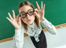 Student with an intelligent expression, correcting glasses. Photo of teen near blackboard, education concept Stock Photo