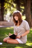 Student with Journal in Park. Pretty brunette student writing in a journal on a university campus Royalty Free Stock Images