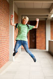 Student jumping up. Happy male high school student jumping up in school Royalty Free Stock Photos