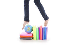 Student jumps over books and globe Royalty Free Stock Images