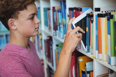 Student keeping digital tablet in bookshelf in library Royalty Free Stock Images