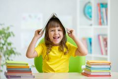 Student kid with a book over her head Stock Photos