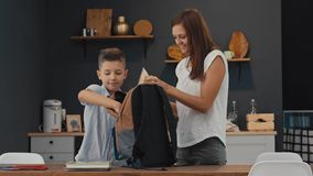 Mother and son prepare a backpack for the first school day stock footage