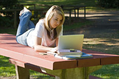 Student on laptop. College age student using laptop listening to electronic device outdoors Royalty Free Stock Photos