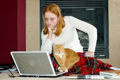 Student with Laptop and cat. Young red head college student studying in front of fireplace with her cat on her lap Stock Photos
