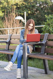 Student laptop computer and sitting on bench in the park. Royalty Free Stock Images