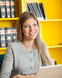 Student With Laptop Smiling Against Bookshelf In Royalty Free Stock Photography