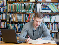 Student with laptop studying in the university library.  Royalty Free Stock Photos
