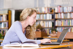 Student with laptop working in library Stock Images