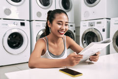 Student in laundromat. Cheerful female student reading magazine in laundromat royalty free stock photo