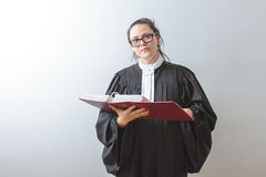 Student of the law. Thirty something brunette woman wearing a canadian lawyer toga reading a red criminal law book Stock Photos