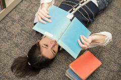 Student laying on carpet with books. Fun young student laying on carpet with a book covering mouth next to a stack of books Royalty Free Stock Image