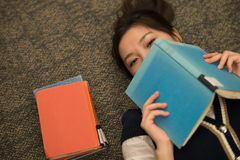 Student laying on carpet with books. Fun young student laying on carpet with a book covering mouth next to a stack of books Royalty Free Stock Photos